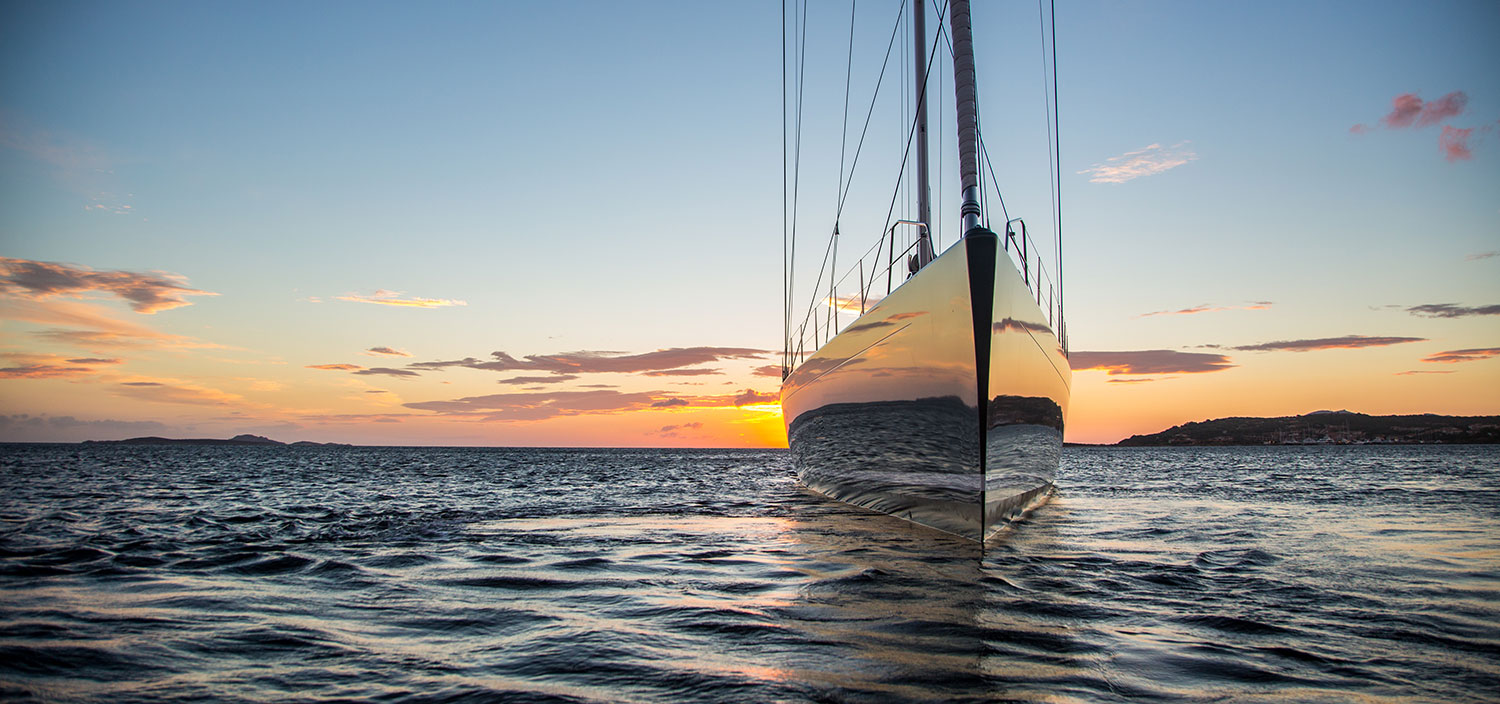 A charter sailing yacht under a setting sun