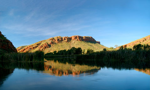 The Kimberley yacht charter region is tranquil with reflective water and orange rocks