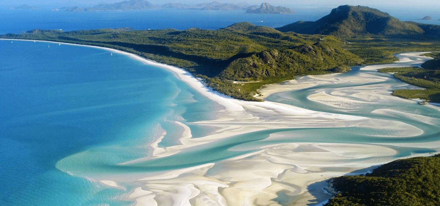 Whitsundays yacht charter itinerary. Swirling sands of a river and ocean of the Whitsunday Island viewed from a luxury yacht charter