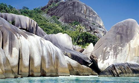 Rocks over the blue seas on a Seychelles yacht charter with Fraser