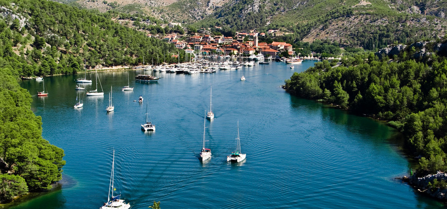 A Croatia yacht charter sails along blue waters by a harbour town