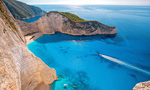 An Ionian Islands yacht charter takes you to quiet beaches with unique rock formations overhanging the sand and water