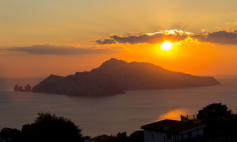 The sun sets dramatically behind an island on a Capri yacht charter