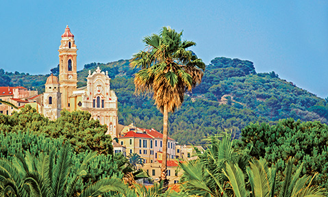 A church and a town are spotted amongst the trees and mountains on a Sardinia yacht charter