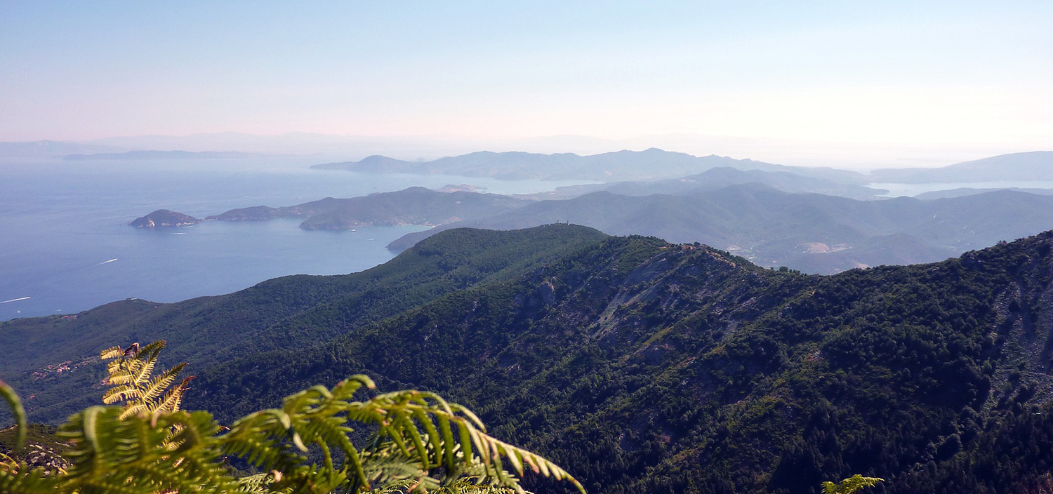 Fraser's Tuscan Archipelago yacht charter sails around lush green mountainous coastlines