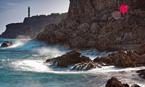 Rough waves hit the rocks with a lighthouse in the background on a Balearics yacht charter