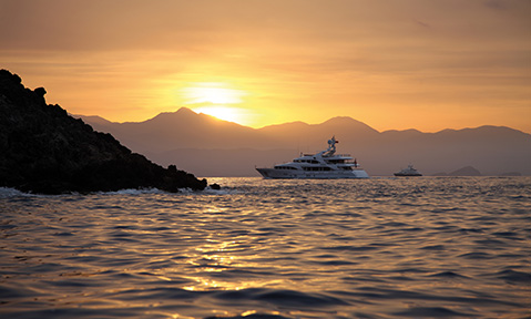 A luxury yacht for charter in Turkey heads towards a bay at sunset