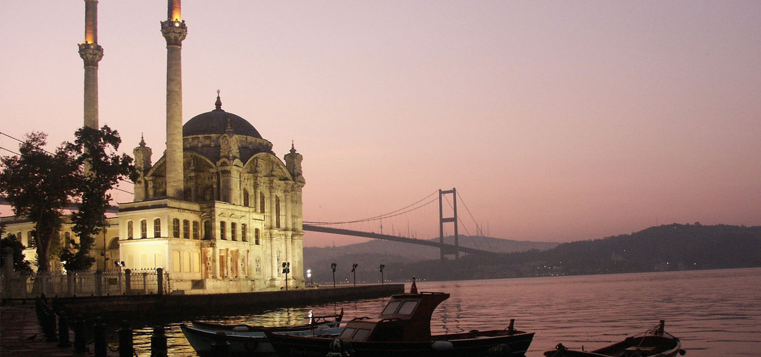 Turkey yacht charter itinerary. Turkish mosque and bridge spanning water in the sunset and yachts for charter
