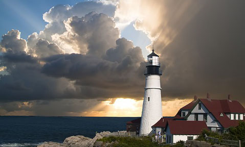 A dramatic sky surrounds a lighthouse seen from a New England yacht charter