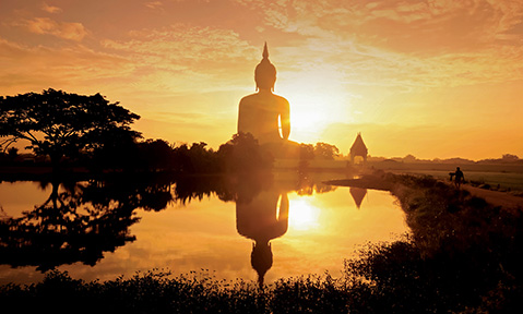 A giant buddha statue faces a temple in the distance over its reflection in still water at sunrise